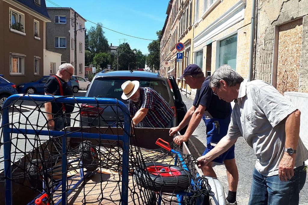 Die Möbelpacker rücken aus für eine Großaktion in Wünschendorf mit Hänger und Sackkarren - bei 35 Grad im Schatten.